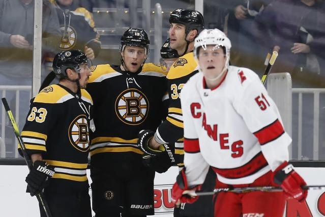 Boston Bruins' Charlie Coyle (13) celebrates his goal as Carolina Hurricanes' Jake Gardiner (51) skates away during the third period of an NHL hockey game in Boston, Tuesday, Dec. 3, 2019. (AP Photo/Michael Dwyer)