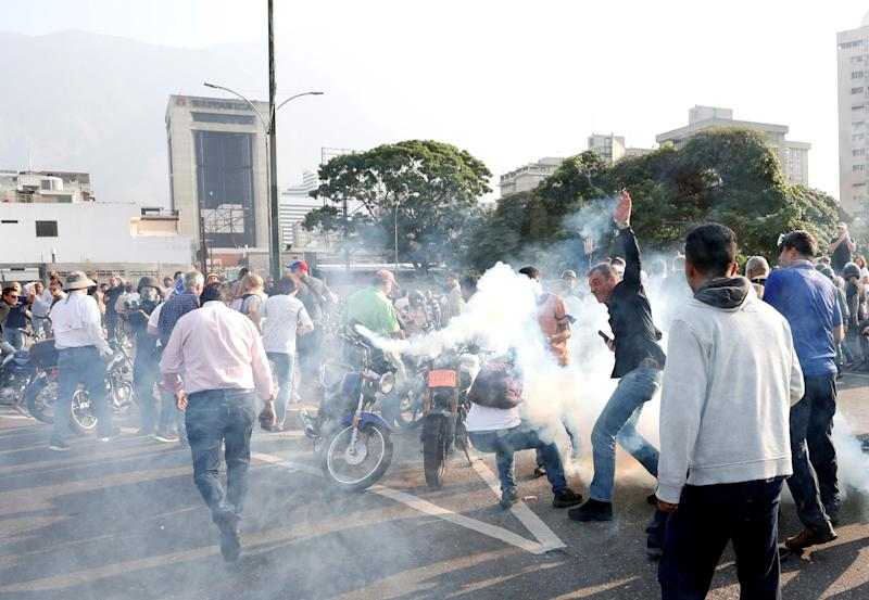 "People react to tear gas near the Generalisimo Francisco de Miranda Airbase ""La Carlota"", in Caracas, Venezuela April 30, 2019. (Photo: Carlos Garcia Rawlins/Reuters)"