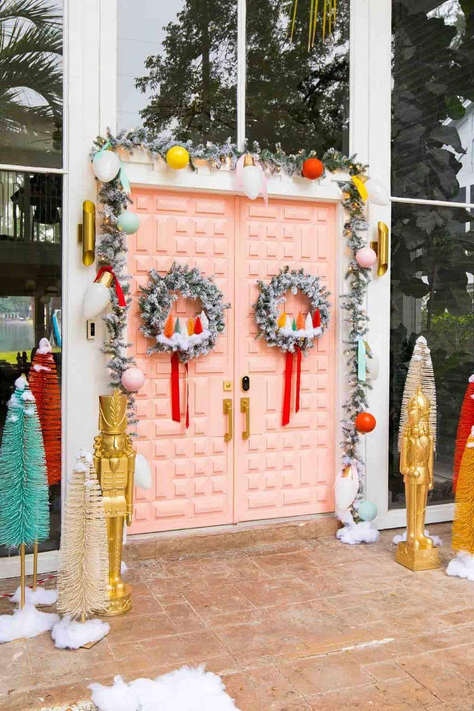 "<p>Tired of the same old red-and-green theme? Think outside the box, like <a href=""https://sugarandcloth.com/our-home-colorful-front-door-christmas-decor/"" rel=""nofollow noopener"" target=""_blank"" data-ylk=""slk:Sugar & Cloth"" class=""link rapid-noclick-resp"">Sugar & Cloth</a> did here with these salmon-pink doors. Funky colored bulbs frame the entryway, while spray-painted toy soldiers and freestanding sisal trees–echoing the smaller ones inside the wreaths–complete the look.</p>"
