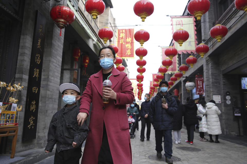 Visitors wearing masks are seen at Qianmen in Beijing, China. Source: AAP