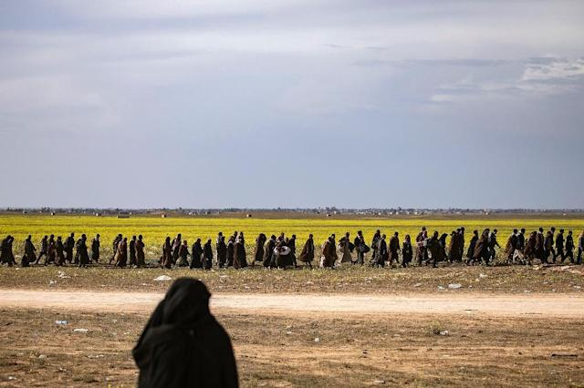 Suspected Islamic State group fighters, many of them wounded, file towards a screening point where they will be interrogated by the US-backed Syrian Democratic Forces (AFP Photo/Delil souleiman)
