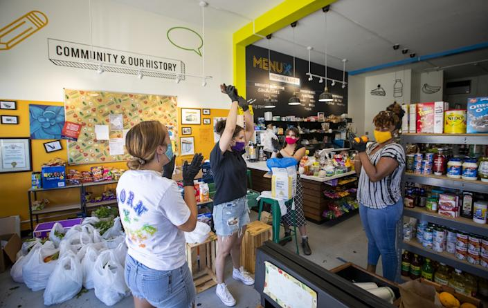 "Luz Arango, second from left, celebrates good news that she received money to help keep her business' doors open for another month with volunteers Nina Angelo, left, Lola Gutierrez, and Osunkoya Chavon, right, while bagging donated food and passing them out to the neighborhood at Lupita's Corner Market And Deli. <span class=""copyright"">(Allen J. Schaben/Los Angeles Times)</span>"