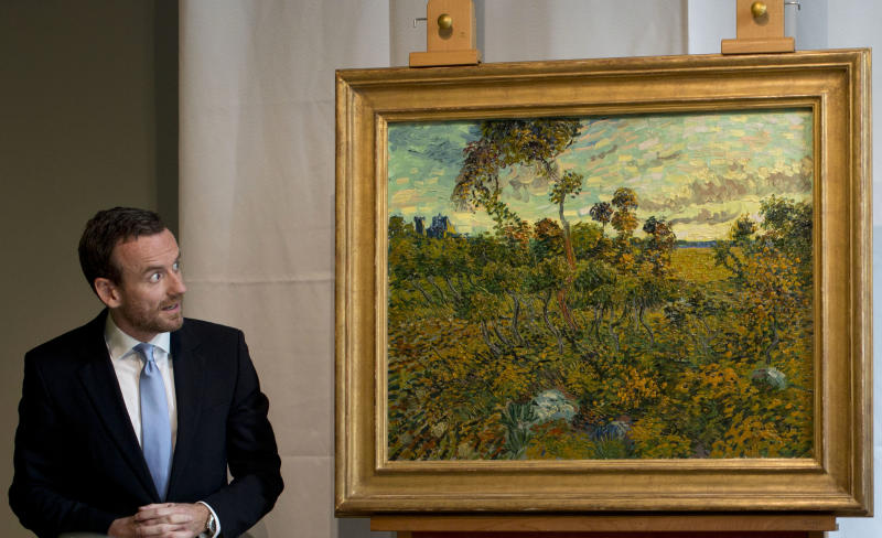 """CAPTION CORRECTION, CORRECTS SPELLING OF SURNAME TO REFLECT AP STYLE - Van Gogh Museum director Axel Rueger, left, looks at """"Sunset at Montmajour"""" after unveiling the painting by Dutch painter Voncent van Gogh during a press conference at the museum in Amsterdam, Netherlands, Monday Sept. 9, 2013. The museum has identified the long-lost painting which was painted by the Dutch mater in 1888, the discovery is the first full size canvas that has been found since 1928 and will be on display from Sept. 24. (AP Photo/Peter Dejong)"""