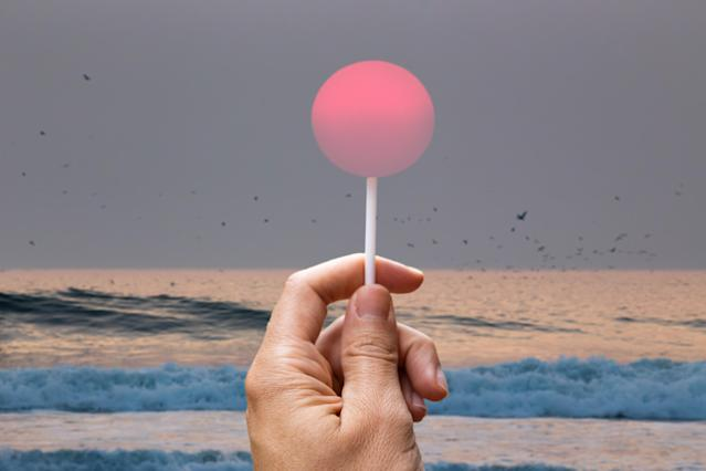 Creative picture of guy holding lollipop stick in the sky matching the setting sun on a California beach.
