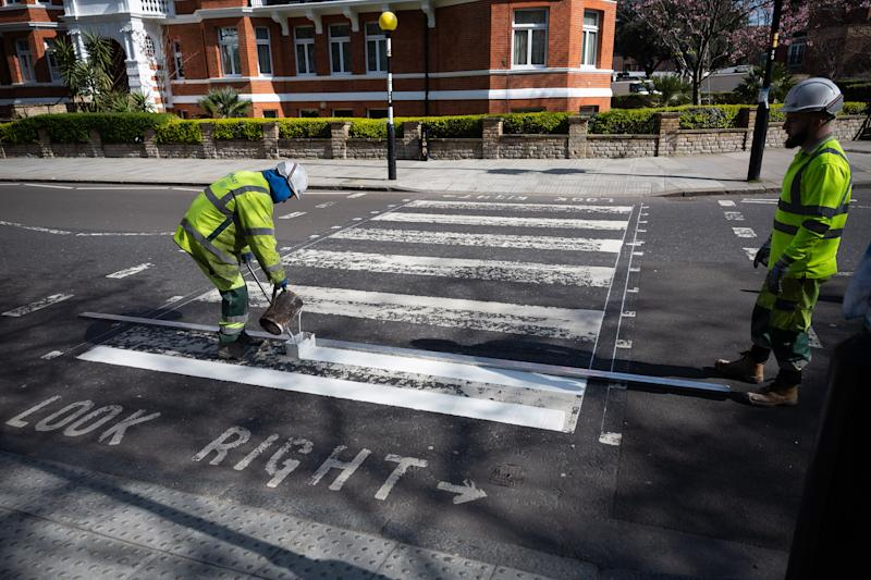LONDON, ENGLAND - MARCH 24: A Highways Maintenance team takes advantage of the COVID-19 coronavirus lockdown and quiet streets to re-paint the iconic Abbey Road crossing on March 24, 2020 in London, England. The Beatles made the pedestrian crossing famous after featuring a photograph of the group walking on it, near to Abbey Road Studios. The album and connected artwork celebrated its fiftieth anniversary last year. British Prime Minister, Boris Johnson, announced strict lockdown measures urging people to stay at home and only leave the house for basic food shopping, exercise once a day and essential travel to and from work. The Coronavirus (COVID-19) pandemic has spread to at least 182 countries, claiming over 10,000 lives and infecting hundreds of thousands more. (Photo by Leon Neal/Getty Images)