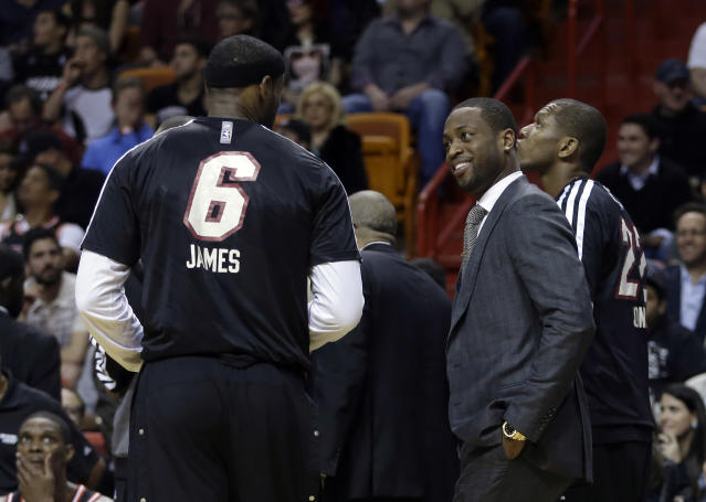 Miami Heat's Dwyane Wade, right foreground, smiles as he talks to teammate LeBron James (6) during a timeout in the first quarter of an NBA basketball game in Miami, Thursday, Jan. 23, 2014. (AP Photo/Alan Diaz)