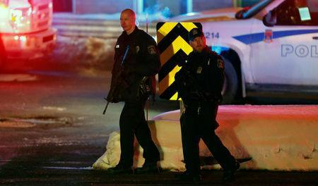 Police officers patrol the perimeter near a mosque after a shooting in Quebec City. REUTERS/Mathieu Belanger