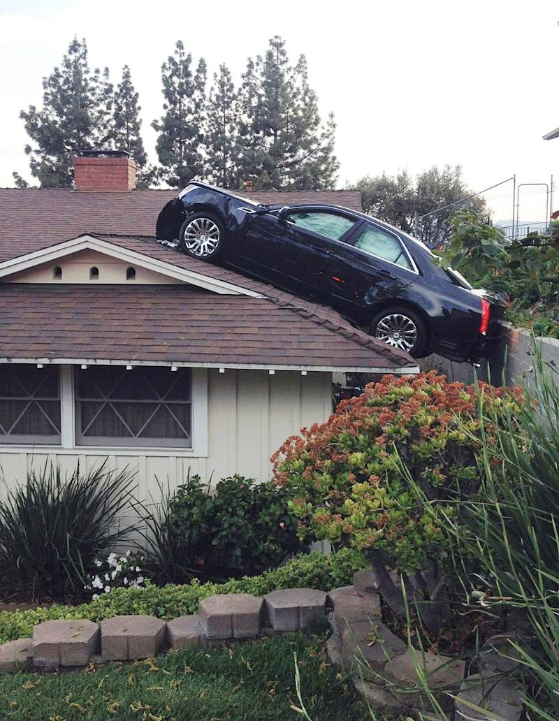 """This photo released by the Glendale Police Department shows a black Cadillac that lost control and careened onto the roof of a neighbor's home on Saturday, March 23, 2013 in Glendale, Calif. The Cadillac driver lost control before leaving his driveway, plunging off a hill """"onto the roof of his neighbor's house directly below his driveway. (Photo courtesy of Glendale Police Department)"""