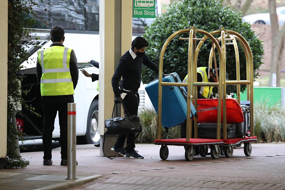 Hotel staff load the luggage of passengers entering quarantine onto trolleys outside the Holiday Inn hotel, near Heathrow Airport (PA Wire)