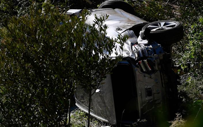 The vehicle driven by golfer Tiger Woods lies on its side in Rancho Palos Verdes, California - GETTY IMAGES