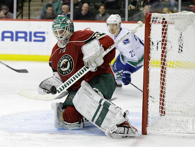 Minnesota Wild goalie Josh Harding (37) deflects a shot by the Vancouver Canucks during the second period of an NHL hockey game in St. Paul, Minn., Tuesday, Dec. 17, 2013. (AP Photo/Ann Heisenfelt)
