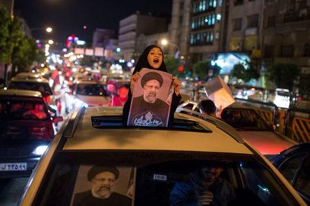 Girl holds a poster of Iranian Presidential candidate Ebrahim Raisi during a campaign rally in Tehran