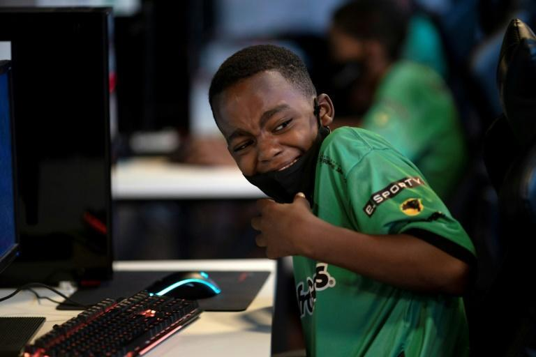 A boy smiles while playing a video game called League of Legends (LoL) at the NGO AfroReggae headquarters