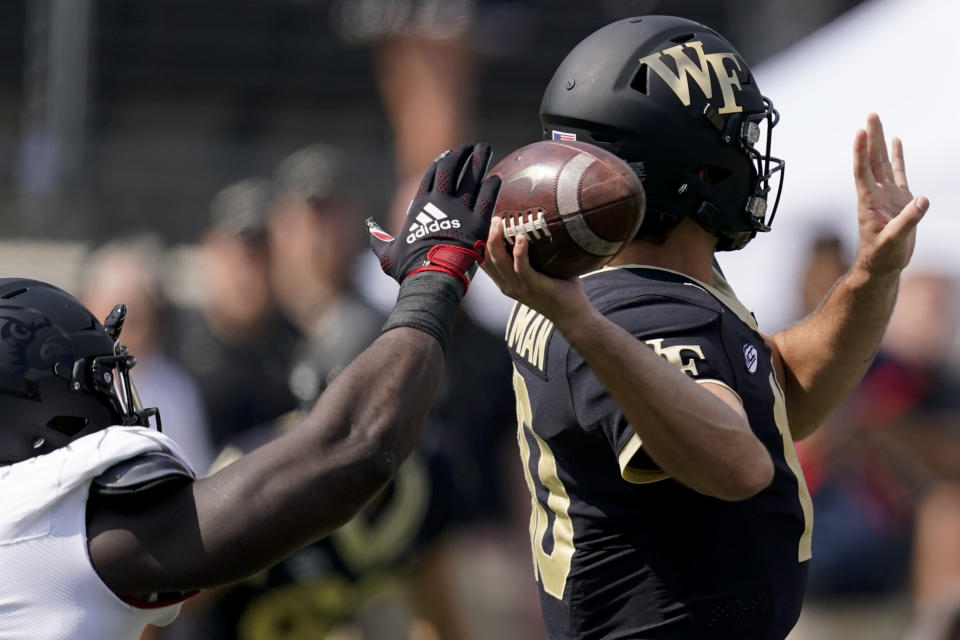 Wake Forest quarterback Sam Hartman passes under pressure by Louisville during the first half of an NCAA college football game on Saturday, Oct. 2, 2021, in Winston-Salem, N.C. (AP Photo/Chris Carlson)