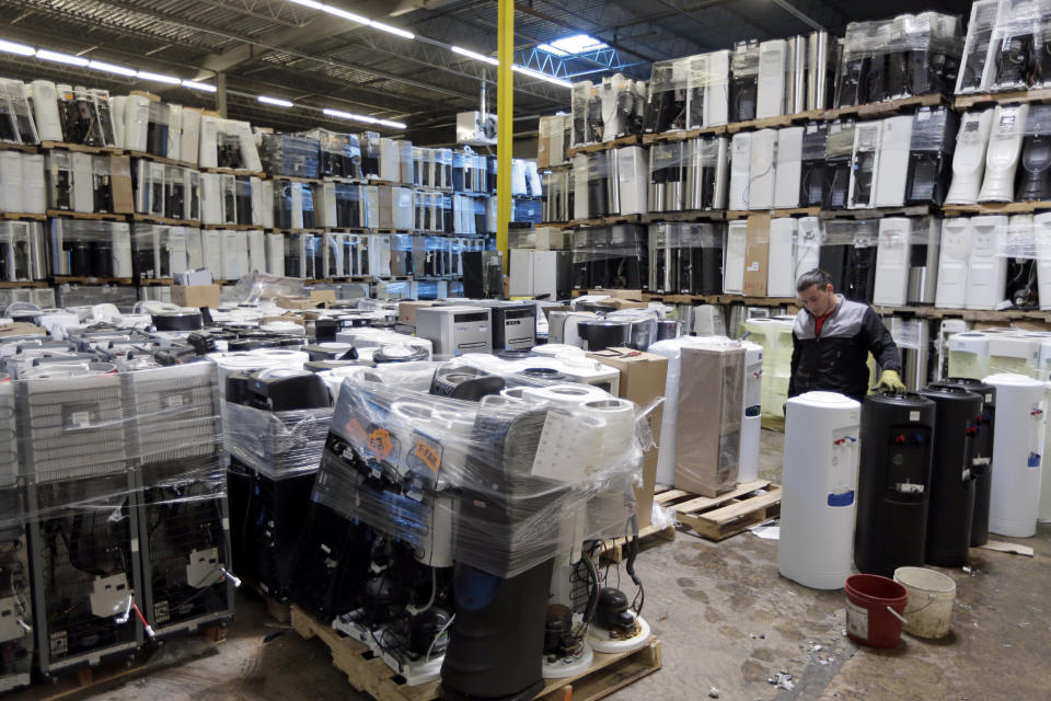 In this May 7, 2019 photo, water coolers are stacked and ready to be broken down into parts for recycling at a GDB International warehouse in Monmouth Junction, N.J. China's decision to restrict scrap imports created big challenges for U.S. recycling programs last year. But it has also spurred investment in plants that process recyclables no longer being shipped overseas. (AP Photo/Seth Wenig)