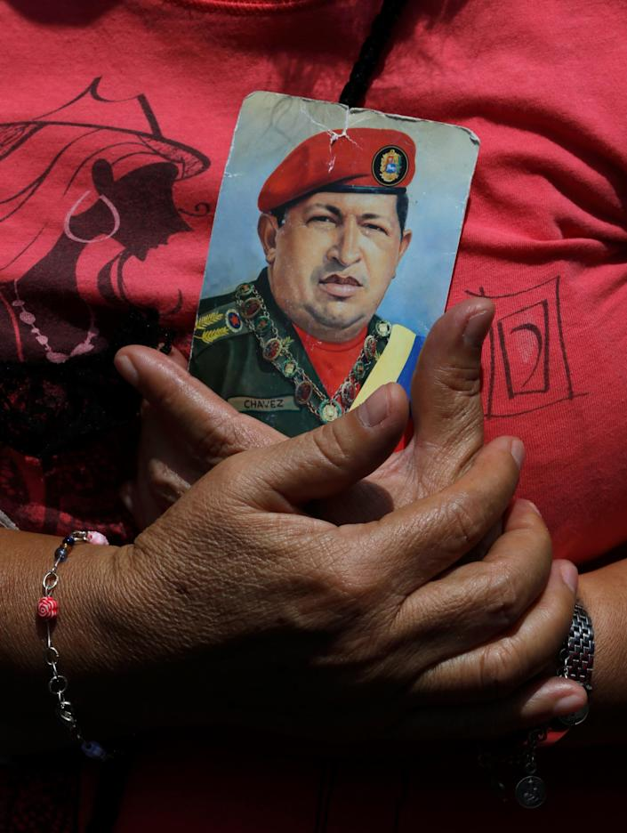 A woman holds a photo of the late President Hugo Chavez during a pro-government rally in Caracas, Venezuela, Saturday, Feb. 22, 2014. Venezuelans on both sides of the nation's political divide took to the streets on Saturday after nearly two weeks of mass protests that have Venezuelan President Nicolas Maduro scrambling to reassert his leadership. (AP Photo/Fernando Llano)