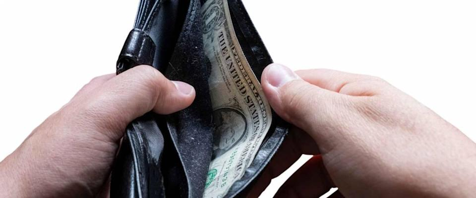 Hands holding almost empty wallet with one dollar. Poverty concept. Financial difficulties concept. Financial crisis, unemployment concept.
