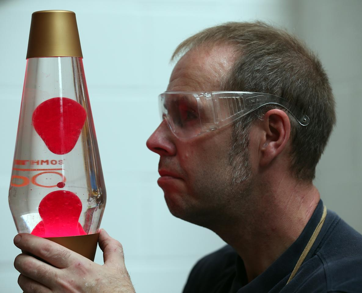 POOLE, ENGLAND - SEPTEMBER 12: Alan Staton looks at a special 50th anniversary lava lamp at the Mathmos factory on September 12, 2013 in Poole, England. The company, based in Poole, Dorset, has been making the lava lamp since 1963, after it's British inventor Edward Craven-Walker was inspired to make it after seeing an odd looking liquid-filled egg timer in a pub. (Photo by Matt Cardy/Getty Images)