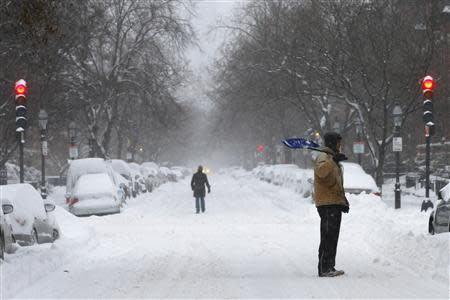 A shoveler stands on Marlborough Street during a winter nor'easter snow storm in Boston, Massachusetts January 3, 2014. REUTERS/Brian Snyder