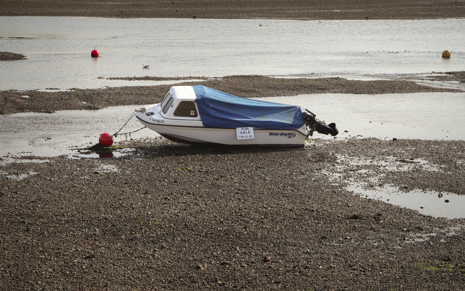 A boat for sale is moored in the Teign estuary during low-tide in Shaldon, Devon, England, Wednesday July 21, 2021. (AP Photo/Tony Hicks)