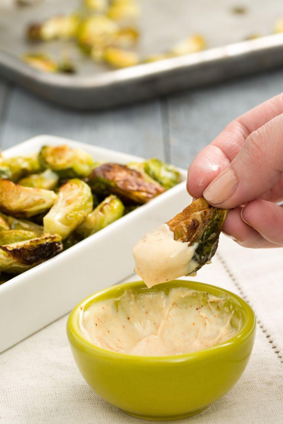 """<p>An appetizer too easy <em>not</em> to make: Roast quartered Brussels sprouts until they're charred and crispy and serve with a three-ingredient aioli. </p><p>Get the recipe from <a href=""""https://www.delish.com/holiday-recipes/thanksgiving/recipes/a44806/crispy-brussels-sprouts-with-spicy-aioli-recipe/"""" rel=""""nofollow noopener"""" target=""""_blank"""" data-ylk=""""slk:Delish"""" class=""""link rapid-noclick-resp"""">Delish</a>. </p>"""