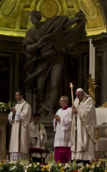 Pope Francis holding a tall, lit, white candle, enters St. Peter's Basilica to begin the Easter vigil service, at the Vatican, Saturday, April 19, 2014. (AP Photo/Alessandra Tarantino)