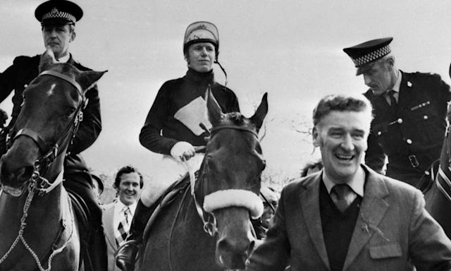 "1974: Red Rum, with jockey Brian Fletcher being led in by trainer Donald ""Ginger"" McCain, after becoming the first horse since ""Reynoldstown"" to win the Grand National in successive years."