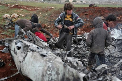 Syrians inspect the wreckage of a regime military helicopter after it was brought down over western Aleppo province