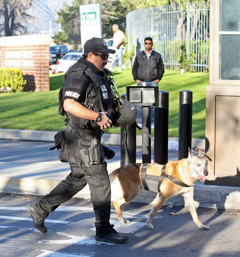 A police officer with a dog walks  through the office building that houses offices of Southern California Edison after a man armed with a rifle shot two people, then shot himself in Irwindale, Calif., Friay, Dec. 16, 2011.  (AP Photo/Ringo H.W. Chiu)