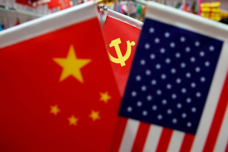 FILE PHOTO: The flags of China, U.S. and the Chinese Communist Party are displayed in a flag stall at the Yiwu Wholesale Market in Yiwu