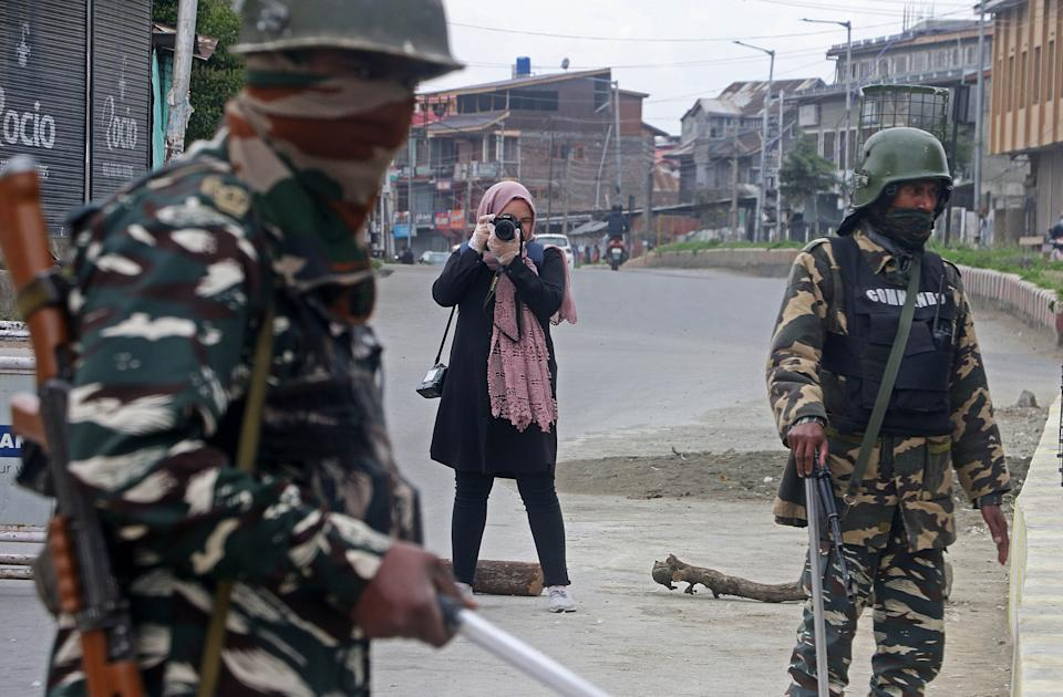 SRINAGAR, INDIA - APRIL 21: Photojournalist Masrat Zahra (Rear) takes photos near a temporary checkpoint before going to Cyber Police Station in Srinagar, Kashmir on April 21, 2020. Indian authorities on Monday booked a Kashmiri photojournalist Zehra under a draconian law for her Facebook post, a move criticized for violating the right to free speech in the worldâs largest democracy. Zahra has been booked under the Unlawful Activities Prevention Act (UAPA) and Section 505 of Indian Penal Code. If convicted, she could face up to seven years in jail. (Photo by Faisal Khan/Anadolu Agency via Getty Images) (Photo: Anadolu Agency via Getty Images)