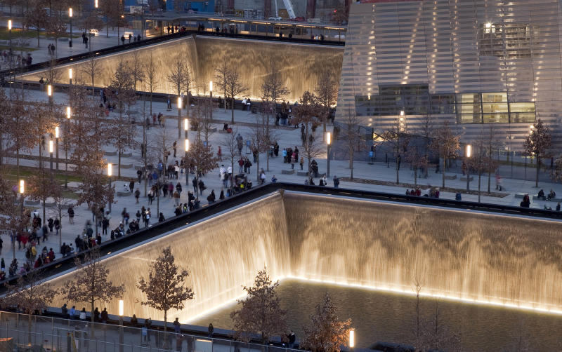 FILE - In this Dec. 20, 2011 file photo, visitors to the National September 11 Memorial in New York walk around its twin pools. The foundation that runs the memorial estimates that once the roughly $700 million project is complete, it will cost $60 million a year to operate. (AP Photo/Mark Lennihan, File)