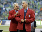 FILE - In this Oct. 4, 2015, file photo, then-Seattle Sounders head coach Sigi Schmid, right, is honored with a red jacket presented by Hank Steinbrecher, left, of the U.S. Soccer Hall of Fame, before an MLS soccer match between the Sounders and the Los Angeles Galaxy, in Seattle. Nearly two years after he died, Schmids presence and influence is being heavily felt heading into Saturdays MLS Cup final between Columbus and Seattle. (AP Photo/Ted S. Warren, File)