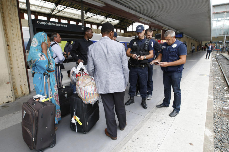 """FILE - In this Sept.15, 2015 file photo, police officers check identity documents at the Saint-Charles train station, in Marseille, southern France. In a first for France, six nongovernmental organizations launched a class-action lawsuit Wednesday, Jan. 27, 2021 against the French government for alleged systemic discrimination by police officers carrying out identity checks. Capitolin, called it a """"mechanical reflex"""" for French police to stop non-whites, a practice he said is damaging to the person being checked and ultimately to relations between officers and the members of the public they are expected to protect. (AP Photo/Claude Paris, File)"""