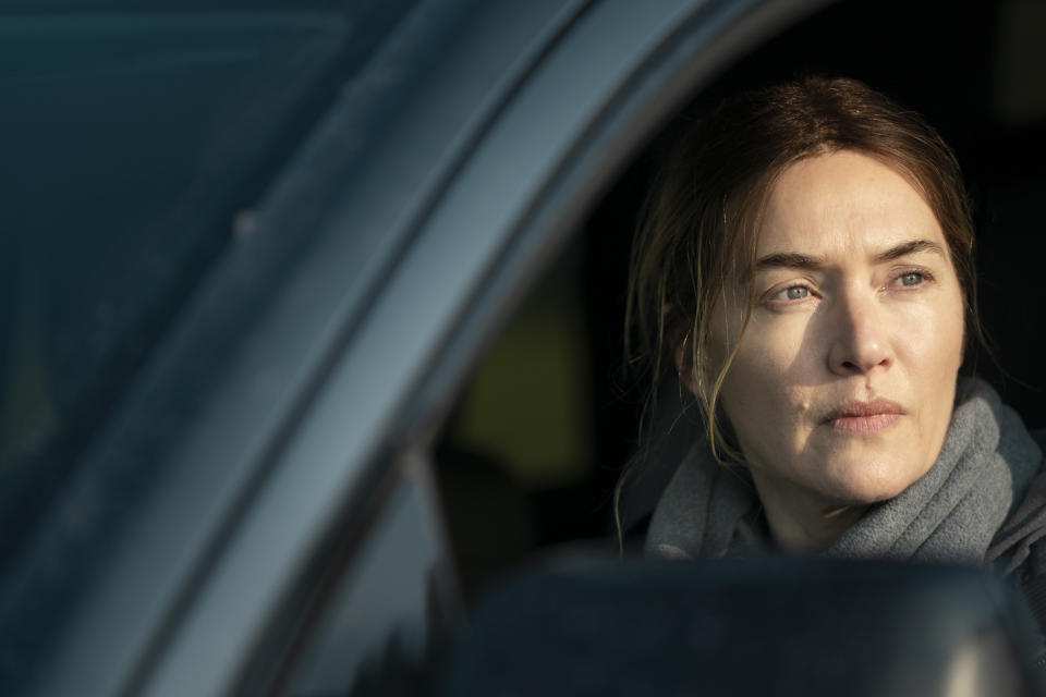 Kate Winslet in character as Mare Sheehan in a car on the set of the Binge TV series Mare of Easttown