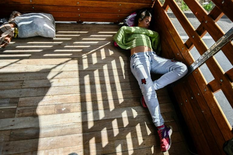Pregnant Venezuelan Mariangela Ascano sleeps in the back of a pick-up truck on her journey south to Ecuador