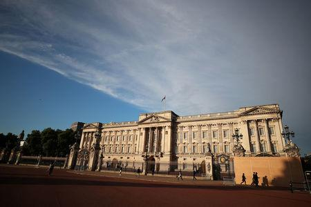 FILE PHOTO: People walk past a protective board outside Buckingham Palace in London