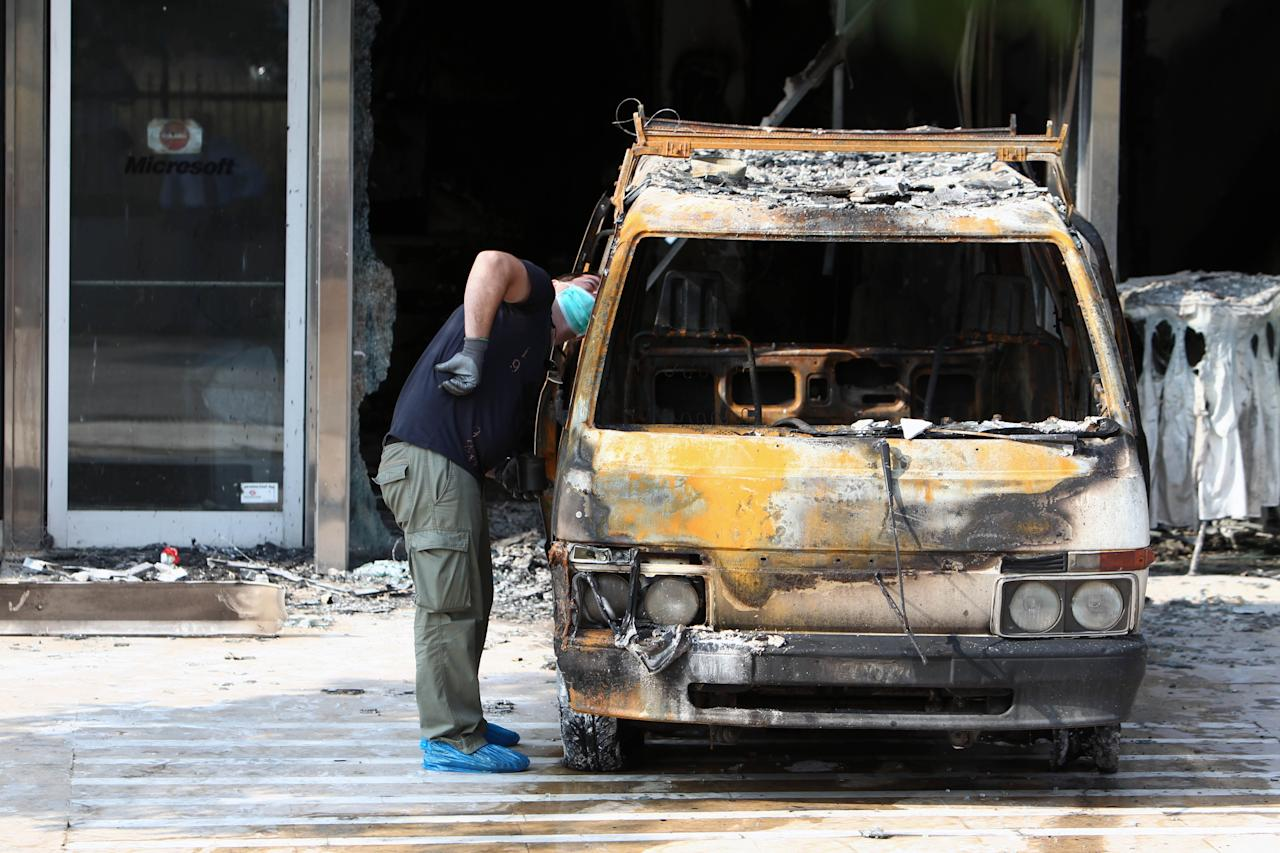 A police officer investigates a destroyed van outside the entrance of Microsoft office in northern Athens, Wednesday, June 27, 2012. Assailants attacked the offices of Microsoft in Athens early Wednesday, driving a van through the front doors and setting off an incendiary device that burned the building entrance, police said. There were no reports of injuries in the pre-dawn attack on the U.S. company's headquarters in the Greek capital, located in the Maroussi suburb north of the city center. (AP Photo/Thanassis Stavrakis)