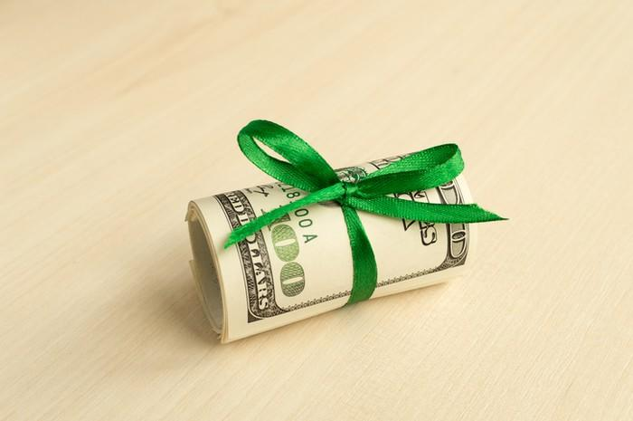 Several $100 bills rolled up and secured with a green ribbon tied in a bow.