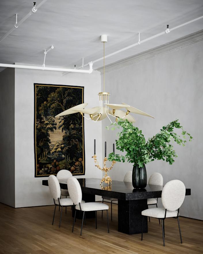 In a nod to Axel Vervoordt's nuanced approach to simplicity, most of the walls were covered in a greige lime wash from Domingue Architectural Finishes. The 14-foot-long dining table was custom made at Paris Ceramics using antiqued, tea-stained marble; the modern chairs, from Artistic Frame, are vaguely reminiscent of Louis XVI fauteuils. A midcentury-style chandelier by Diego Mardegan for Glustin Luminaires completes the timeless look.