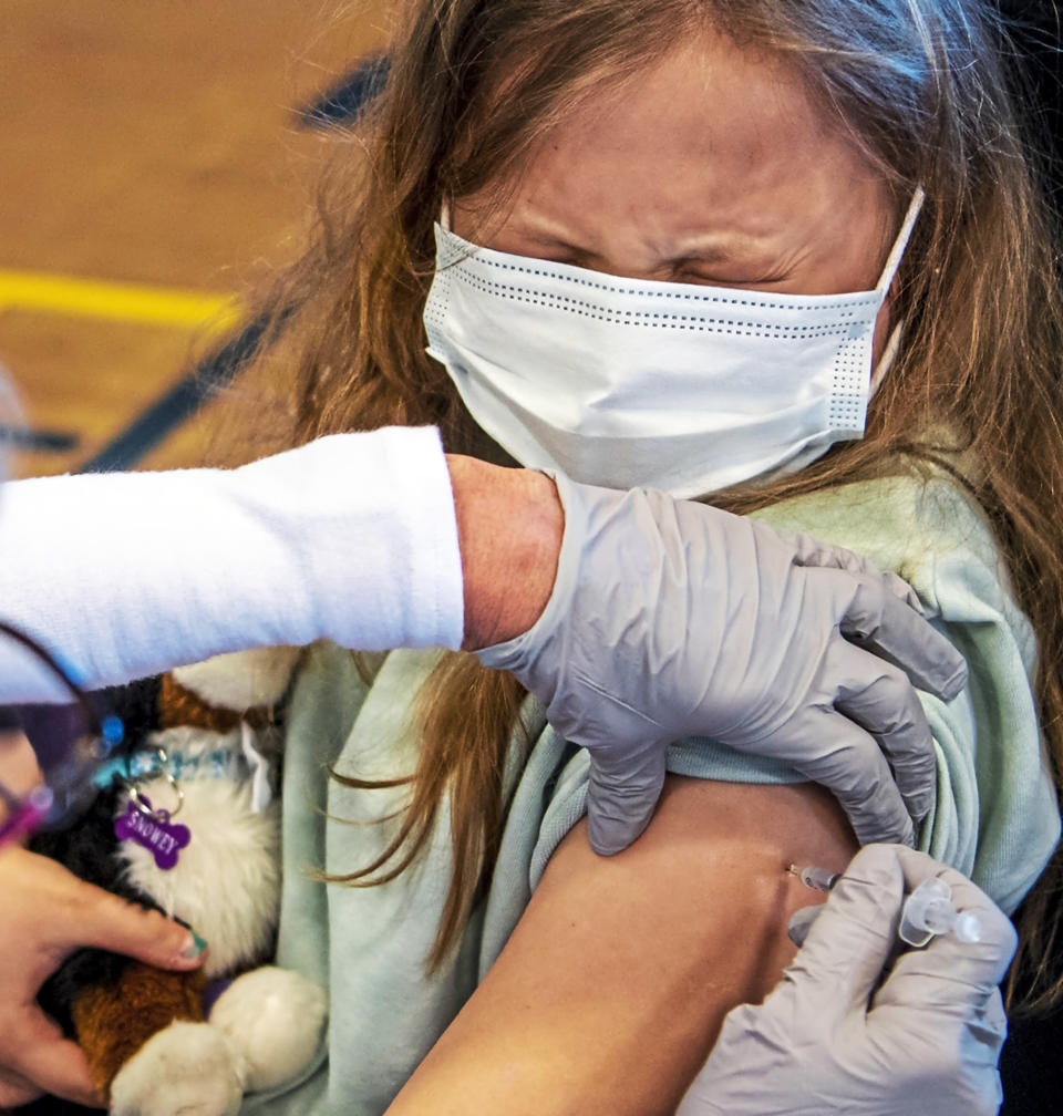Linda Zeigler, of nurse with St. Clair Health, administers the Pfizer COVID-19 vaccine to Anita Murphy, 12, of Brookline, at a clinic organized by St. Clair Health and the Carnegie Boys and Girls Club to vaccinate youth ages 12 and older, Saturday, May 15, 2021, in Carnegie, Pa. (Alexandra Wimley/Pittsburgh Post-Gazette via AP)