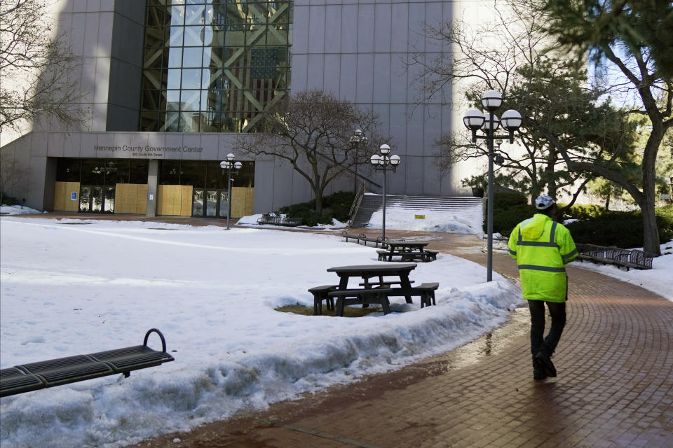 A worker walks the path leading to the boarded-up south entrance of the Hennepin County Government Center, Wednesday, Feb. 23, 2021, in Minneapolis, where the trial of former Minneapolis police officer Derek Chauvin is scheduled to begin with jury selection March 8. Chauvin is charged with murder the death of George Floyd during an arrest last May in Minneapolis. (AP Photo/Jim Mone)