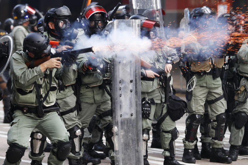 FILE - In this Oct. 1, 2019, file photo, police fire tear gas to disperse anti-government protesters in Hong Kong. Underground networks of volunteer medics have sprung up in Hong Kong to treat wounded protesters who fear arrest if they go to government hospitals. (AP Photo/Vincent Thian, File)