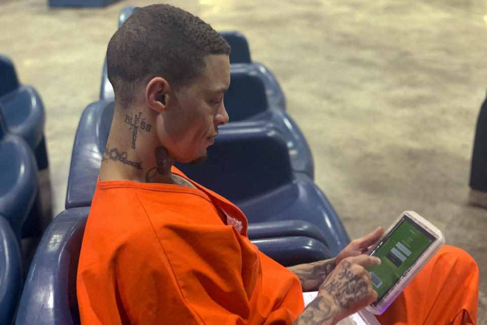 In a photo provided by the North Fork Correctional Center in Sayre, Oklahoma on Tuesday, June 9, 2021, inmate Byron Robinson works on a new Securus tablet, which are being provided for free to Oklahoma inmates as part of a new program by the Department of Corrections. Robinson, who has been incarcerated since 2005, the same year YouTube was founded, said it was the first time he'd ever held a computer tablet. The devices will include free content like access to a law library, along with some podcasts, books and educational materials. (Lance West/Oklahoma Department of Corrections via AP)