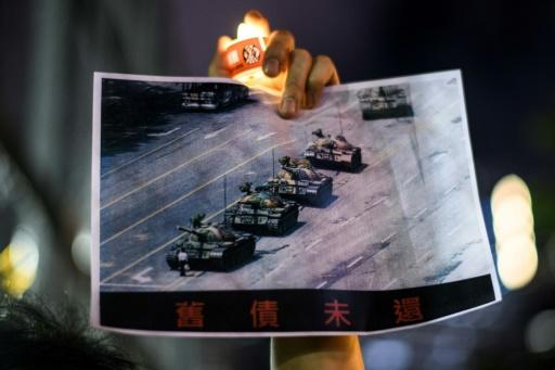 A man at a 2020 commemoration in Hong Kong holds a poster of the famous 'Tank Man' standing in front of Chinese military tanks in Tiananmen Square in 1989