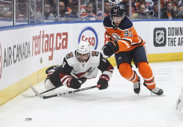 Arizona Coyotes ' Vinnie Hinostroza (13) is tripped by Edmonton Oilers' Ryan Nugent-Hopkins (93) during first-period NHL hockey game action in Edmonton, Alberta, Monday, Nov. 4, 2019. (Jason Franson/The Canadian Press via AP)