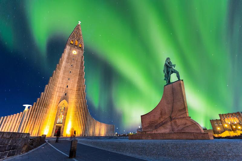 Aurora borealis above Hallgrimskirkja Church in central of Reykjavik city in Iceland | basiczto—Getty Images/iStockphoto