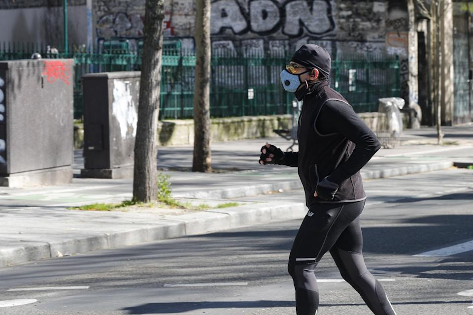 PARIS, FRANCE - MARCH 25: A man wears a medical mask within precautions against coronavirus as he runs in a street in Paris, France on March 25, 2020. (Photo by Geoffroy Van Der Hasselt/Anadolu Agency via Getty Images)