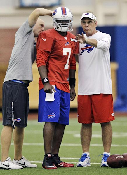 New acquired Buffalo Bills quarterback Tarvaris Jackson (7) talks with quarterbacks coach David Lee, right, as an equipment staffer adjusts Jackson's helmet during NFL football practice in Orchard Park, N.Y., Monday, Aug. 27, 2012. Shortly after announcing they had released Vince Young, the Bills followed up to confirm reports that they had acquired Jackson in a trade with the Seattle Seahawks in exchange for an undisclosed draft pick. (AP Photo/David Duprey)