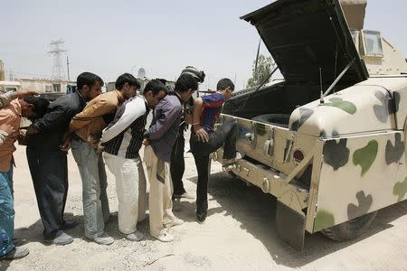 Personnel from the Iraqi security forces detain suspected militants of the al Qaeda-linked Islamic State in Iraq and the Levant, during a raid operation in Jurf al-Sakhar, in this May 27, 2014 file photo. REUTERS/Mushtaq Muhammed/Files